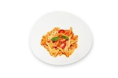 Pastas con el tomate en el plato blanco aislado imagen de archivo