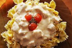 Pastas con la salsa del pollo y de queso, tomates de cereza Imagen de archivo libre de regalías