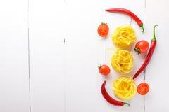 Pastas con las verduras, los tomates de cereza, las pimientas de chile y ajo En un fondo de madera Espacio libre para el texto Vi Imagen de archivo libre de regalías