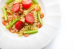 Pastas con las verduras y las gambas en la opinión superior de la placa blanca Fotos de archivo libres de regalías