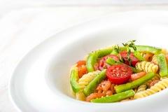 Pastas con las verduras y los camarones en la placa blanca horizontal Imágenes de archivo libres de regalías