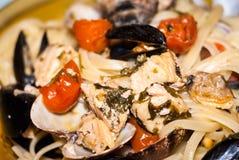Pastas con los peces espadas y los tomates Foto de archivo libre de regalías