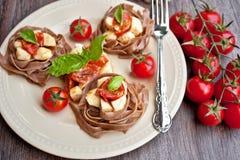 Pastas con los tomates de cereza y la mozarela Fotografía de archivo libre de regalías