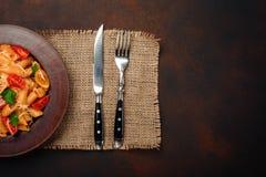 Pastas con queso, el tomate de cereza, la bifurcación y el cuchillo en fondo oxidado foto de archivo