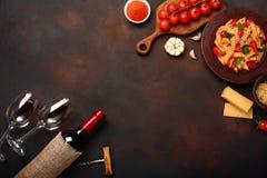 Pastas con queso, salsa de tomate de cereza, la copa y el vino de la botella, sacacorchos, ajo, cúrcuma en fondo oxidado fotos de archivo libres de regalías