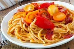 Pastas cremosas de la calabaza moscada con el primer de los tomates del tocino y de cereza fotografía de archivo