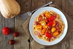 Pastas cremosas de la calabaza moscada con tocino y tomates sobre la madera fotos de archivo libres de regalías