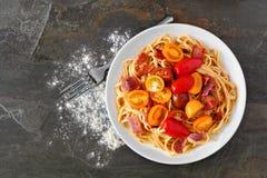 Pastas cremosas de la calabaza moscada con tocino y tomates sobre pizarra imagenes de archivo