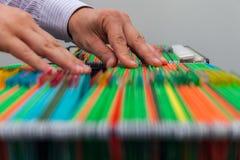 Pastas de arquivos de suspensão coloridas do fundo abstrato na gaveta Mãos masculinas que olham o original em uma pilha inteira d Imagem de Stock Royalty Free