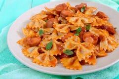 Pastas de Farfalle con los pedazos de la salchicha en salsa de tomate Foto de archivo libre de regalías