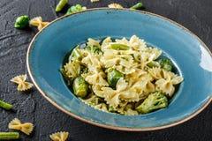 Pastas de Farfalle del vegano en una salsa de la espinaca con el bróculi, coles de Bruselas, habas verdes en placa en fondo de pi fotos de archivo