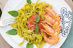 Pastas de la espinaca con los camarones y la salsa de tomate Imagen de archivo