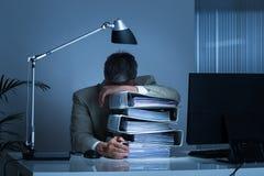 Pastas de Leaning Head On do homem de negócios ao trabalhar tarde foto de stock royalty free