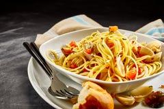 Pastas de los espaguetis con las almejas servidas con el rollo de pan Imagenes de archivo