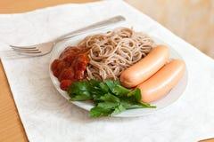 Pastas de los espaguetis con las salchichas y la salsa de tomate Foto de archivo