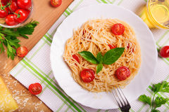 Pastas de los espaguetis con los tomates y el perejil en la tabla foto de archivo libre de regalías