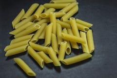 Pastas de los macarrones en fondo negro fotografía de archivo
