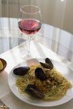 Pastas de los mejillones con la copa de vino roja Foto de archivo