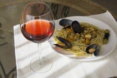 Pastas de los mejillones con la copa de vino roja horizontal Imagen de archivo