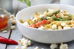 Pastas de Penne con el espárrago, el queso de soja ahumado, pimientas de chiles y mini cebollas del maíz en salsa de la nuez fotografía de archivo libre de regalías