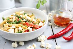 Pastas de Penne con el espárrago, el queso de soja ahumado, pimientas de chiles y mini cebollas del maíz en salsa de la nuez fotos de archivo
