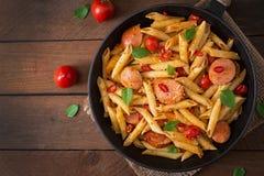 Pastas de Penne con la salsa de tomate con la salchicha, tomates, albahaca verde adornada en un sartén Foto de archivo libre de regalías