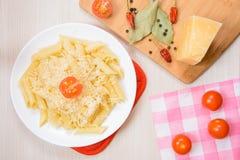 Pastas de Penne con queso rallado en una placa redonda blanca al lado de las especias y de los tomates en la tabla Fotos de archivo
