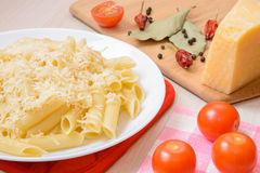 Pastas de Penne con queso rallado en una placa redonda blanca al lado de las especias y de los tomates en la tabla Imagenes de archivo