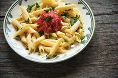 Pastas de Penne en la salsa de tomate, tomates adornados con perejil en un fondo de madera Fotografía de archivo libre de regalías