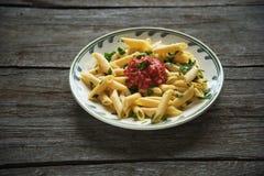 Pastas de Penne en la salsa de tomate, tomates adornados con perejil en un fondo de madera Imagen de archivo