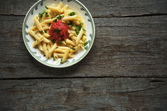 Pastas de Penne en la salsa de tomate, tomates adornados con perejil en un fondo de madera Imagenes de archivo