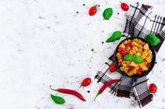 Pastas de Radiatori con el pollo y pimientas en el fondo blanco Visión superior Foto de archivo