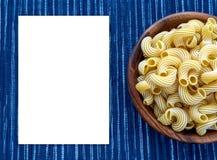 Pastas de Rigati en un cuenco de madera en un fondo azul blanco rayado del paño con un lado Espacio blanco para el texto y las id Imagen de archivo