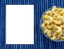 Pastas de Rigati en una taza de cristal en un fondo azul blanco rayado del paño con un lado Espacio blanco para el texto y las id Fotos de archivo