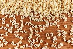 Pastas del alfabeto en el fondo de madera Fotos de archivo
