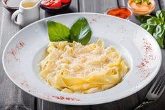 Pastas del Fettuccine con el queso parmesano, la albahaca y la salsa cremosa en fondo de madera oscuro imagen de archivo