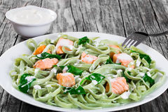Pastas del Fettuccine de los salmones y de la espinaca en los platos blancos imagen de archivo