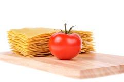 Pastas del Lasagna con el tomate en la tarjeta de corte Foto de archivo