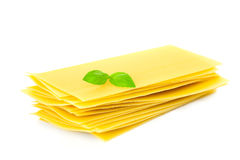 Pastas del Lasagna con la puntilla de la hoja de la hierba de la albahaca aislada Imagenes de archivo
