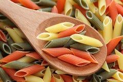 Pastas del rigate de Penne en una cuchara de madera Imagen de archivo libre de regalías