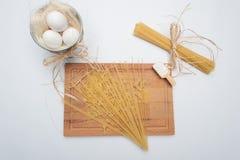 Pastas en el tablero de madera con la harina y el huevo Fotografía de archivo libre de regalías