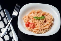Pastas en salsa de tomate en un fondo negro imagen de archivo libre de regalías