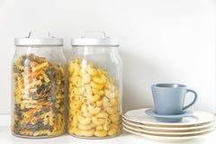 Pastas en una taza del tarro y de café en cocina fotos de archivo