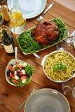 Pastas, ensalada vegetal y pollo asado en la tabla Imágenes de archivo libres de regalías