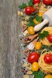 Pastas, especias, hierbas y tomates en un fondo de madera Foto de archivo libre de regalías