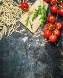 Pastas frescas con los tomates, el parmesano y el arugula en el fondo rústico, visión superior, frontera Fotografía de archivo