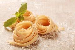 Pastas frescas planas rodadas del Fettuccine en la tabla Imagen de archivo