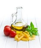 Pastas italianas con albahaca, los tomates y el aceite de oliva Foto de archivo