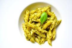 Pastas italianas con pesto de la albahaca en una placa blanca Foto de archivo