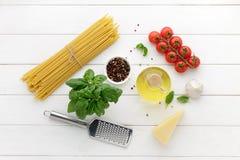 Pastas italianas crudas con los tomates, aceite, albahaca en el fondo de madera blanco listo para guisar Imagenes de archivo